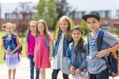 Grand portrait d'élève d'école en dehors des sacs de transport de salle de classe Photos stock