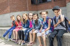 Grand portrait d'élève d'école en dehors des sacs de transport de salle de classe Image stock