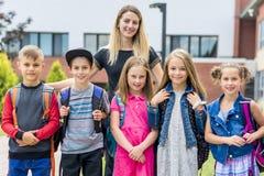 Grand portrait d'élève d'école en dehors des sacs de transport de salle de classe avec le professeur Photos stock