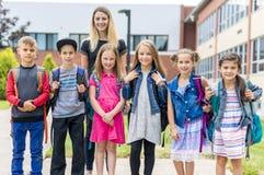 Grand portrait d'élève d'école en dehors des sacs de transport de salle de classe avec le professeur Photo stock
