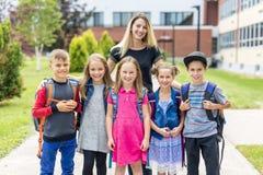 Grand portrait d'élève d'école en dehors des sacs de transport de salle de classe avec le professeur Photo libre de droits