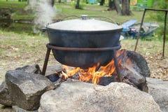 Grand pot en métal avec un couvercle et une poignée sur le trépied utilisé pour la cuisson Cuisson dans un chapeau de lanceur sur photo libre de droits