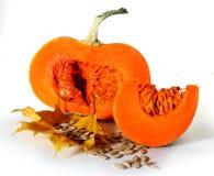 Grand potiron orange de thanksgiving avec la tranche et graines sur des feuilles d'automne Images stock