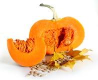 Grand potiron orange de thanksgiving avec la tranche et graines sur des feuilles d'automne Image libre de droits