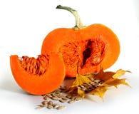 Grand potiron orange-foncé de thanksgiving avec la tranche et graines sur des feuilles d'automne Images libres de droits