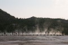 Landscape of Yellowstone boardwalk with silhouetted tourists walking in steam royalty free stock photos