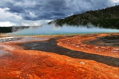 Grand prismatic spring. Summer time clouds, steam and bacteria provide interesting colors to the Grand prismatic geyser in Yellowstone park Royalty Free Stock Photo