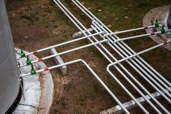 Grand réservoir de stockage de pétrole avec des valves et des tuyauteries Photos libres de droits
