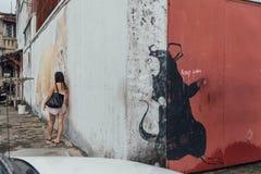Grand rat noir peint entre le mur blanc et rouge de la rue de George Town Penang, Malaisie Image stock