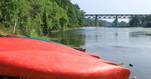 Grand River at Paris, Ontario, Canada with canoes in foreground 4K stock video footage