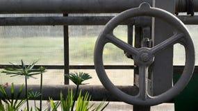 Grand robinet avec la valve de fermeture de tuyau dans le conservatoire photographie stock libre de droits
