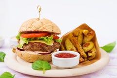 Grand sandwich - hamburger avec l'hamburger juteux de boeuf, le fromage, la tomate, et l'oignon rouge Photo libre de droits