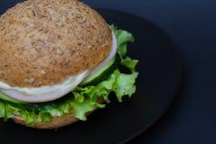 Grand sandwich - hamburger fait maison avec de la viande, le fromage, la tomate, et l'oignon juteux de poulet sur le fond noir images libres de droits
