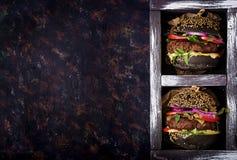 Grand sandwich noir - hamburger noir avec l'hamburger juteux de boeuf, le fromage, la tomate, et l'oignon rouge dans la boîte photos libres de droits
