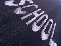 Grand signe d'ÉCOLE peint sur une rue urbaine Photographie stock