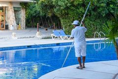 Grand Sirenis Hotel & Spa, Riviera Maya, Mexico, DECEMBER 24, 2017 - A man, personnel cleaning the pool at a tropical resort. stock photo
