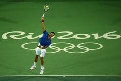 Grand Slam champion Novak Djokovic of Serbia in action during men`s singles first round match of the Rio 2016 Olympic Games Royalty Free Stock Photo