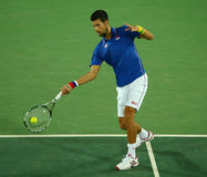 Grand Slam champion Novak Djokovic of Serbia in action during men`s singles first round match of the Rio 2016 Olympic Games Royalty Free Stock Photography