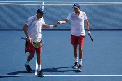 Grand Slam champions Mike and Bob Bryan of United states in action during US Open 2017 round 3 men`s doubles match. NEW YORK -SEPTEMBER 4, 2017: Grand Slam Stock Photo