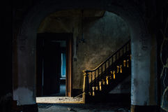Grand Staircase at Foyer - Abandoned House. A depressing view of the foyer with a grand staircase, accented by a wood banister, flanked by cracked plaster, at a royalty free stock photo