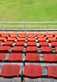 Grand stand, seat in stadium. Grand stand, orange seat and green field in stadium. (vertical view stock image