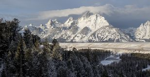 Grand teton above snake river plains and forests on ominous win. Mountain range rises above a river, forest, and plains on a winter morning in Grand Teton stock photos