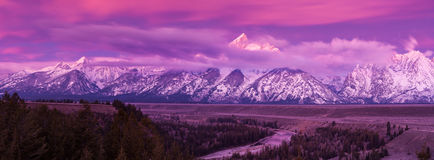 Grand Teton mountains at dawn. Dawn breaks with a purple glow revealing low clouds on the Teton mountains seen from the Snake River overlook in Grand Teton Stock Image