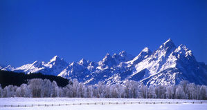 Grand Tetons. Countryside fence and the Grand Tetons in winter stock photo