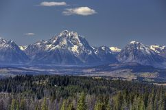 Grand Tetons and evergreen forest stock photography