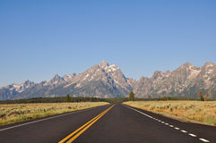 The Grand Tetons. Long straight road with mountain view in Grand Teton National Park Stock Images
