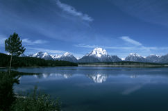 Grand Tetons Reflected in Jackson Lake. Snowbound peaks of the Grand Tetons are mirrored in the deep blue waters of Jackson Lake in northwestern Wyoming. One of Royalty Free Stock Photography