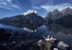 Grand Tetons Reflected in Jenny Lake. Snowbound peaks of the Grand Tetons are mirrored in the deep blue waters of Jenny Lake in northwestern Wyoming. Rocky Stock Image