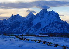 Grand Tetons split rail fence view at alpenglow twilight sunset under lenticular clouds in Grand Tetons National Park in Wyoming Stock Image