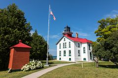 Grand Traverse Light on Leelanau Peninsula, Michigan. During daytime. Blue sky and clouds in the background. An american flag on flagpole stock image