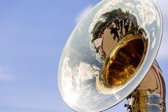Grand tuba en laiton avec des réflexions contre le ciel bleu Images stock