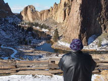 Grand view at Smith Rocks State Park. A woman in a fuzzy purple hat enjoys the grand view at Smith Rocks State Park in Central Oregon with the snowy jagged and Royalty Free Stock Photography