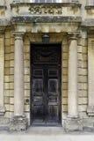 Grand wooden door between stone pillars Royalty Free Stock Images