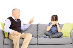 Grandad που φωνάζει στον ανηψιό του, που κάθεται σε έναν καναπέ Στοκ Φωτογραφίες
