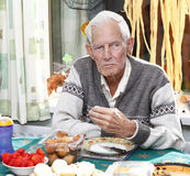 Elderly man eating. Elderly senior man eating at a party Stock Images