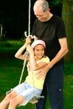 Grandad e ragazza da oscillazione Immagine Stock