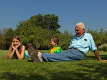 Grandad and grandchildren. Grandfather and grandchildren smiling over the grass royalty free stock image