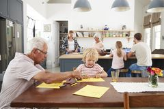 Grandad and grandson drawing together in busy family kitchen royalty free stock photography