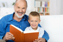 Grandad and grandson enjoying a book together. Elderly granfather and grandson enjoying a book together as they sit reading on a couch in the living room royalty free stock photos