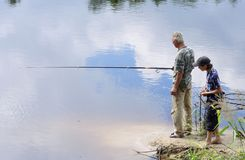 Grandad and grandson fishing. Looking down on grandfather and grandson fishing in lake Stock Photography
