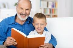Grandad i wnuk cieszy się książkę wpólnie Zdjęcia Royalty Free