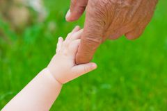 Grandad's and baby's hands Royalty Free Stock Images