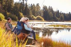 Grandad teaches his grandson to fish at a lake, dad watching Stock Image