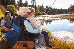Grandad teaches his grandson to fish at a lake, dad watching Stock Photos