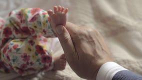 Grandad touching feet of baby grandchild