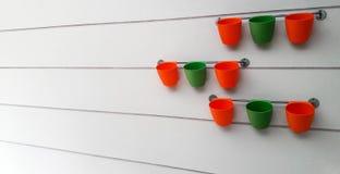 Grandangolare dei vasi da fiori variopinti con fondo grigio Fotografia Stock